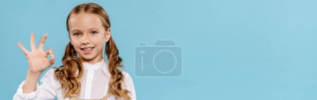 Photo for Panoramic shot of smiling and cute kid looking at camera and showing ok isolated on blue - Royalty Free Image