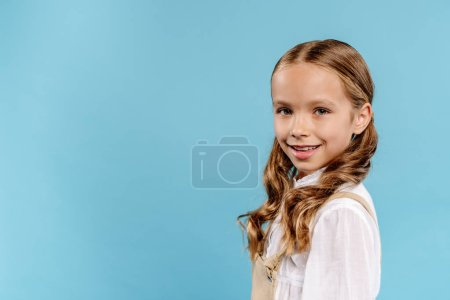 Photo pour Un enfant souriant et mignon regardant une caméra isolée en bleu - image libre de droit