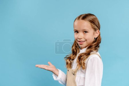 Photo pour Smiling and cute kid with outstretched hand looking at camera isolated on blue - image libre de droit
