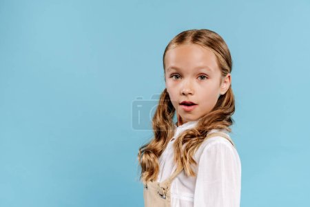 Photo for Shocked and cute kid looking at camera isolated on blue - Royalty Free Image