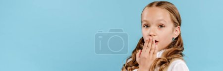 panoramic shot of shocked and cute kid looking at camera and obscuring face isolated on blue