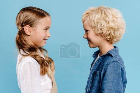 Foto de Vista lateral de niños sonrientes y lindos mirándose unos a otros aislados en azul. - Imagen libre de derechos