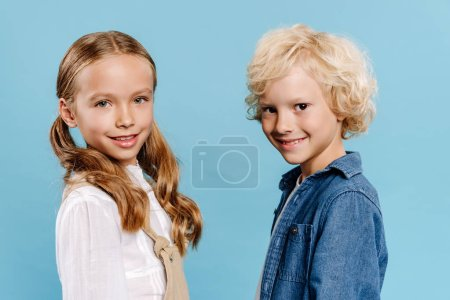 Photo for Smiling and cute kids looking at camera isolated on blue - Royalty Free Image