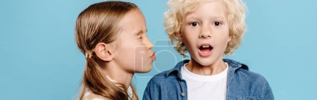 Photo for Panoramic shot of kid kissing shocked friend isolated on blue - Royalty Free Image