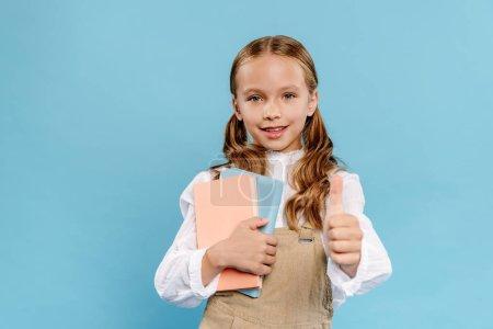 Photo pour Un enfant souriant et mignon montrant comme un geste et tenant des livres isolés sur bleu - image libre de droit