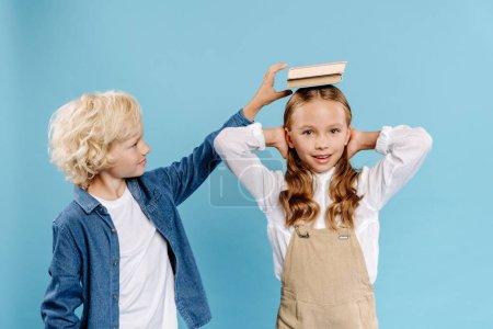 Photo pour Garçon mettant un livre sur la tête de son ami souriant isolé sur bleu - image libre de droit