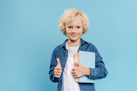 Photo for Smiling and cute kid showing like gesture and holding books isolated on blue - Royalty Free Image