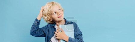 Foto de Plano panorámico de niño sonriente y soñador sosteniendo libros aislados en azul - Imagen libre de derechos