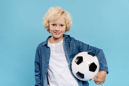 Photo for Smiling and cute kid looking at camera and holding football isolated on blue - Royalty Free Image