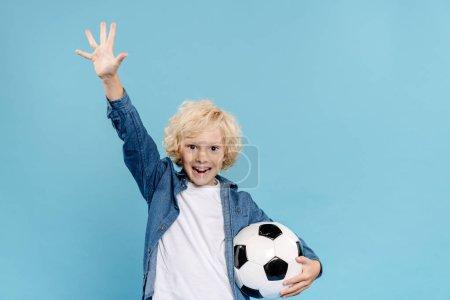 Photo pour Enfant souriant et mignon avec la main tendue regardant la caméra et tenant le football isolé sur bleu - image libre de droit