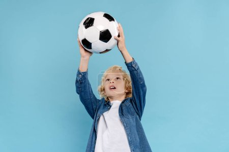 Photo for Cute kid playing with football isolated on blue with copy space - Royalty Free Image