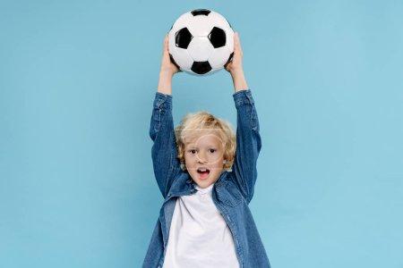 Photo pour Mignon enfant tenant football et hurlant isolé sur bleu - image libre de droit