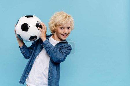 Photo pour Enfant souriant et mignon regardant la caméra et tenant le football isolé sur bleu - image libre de droit