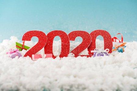 Photo pour Numéros 2020 et boîtes cadeaux de Noël dans la neige blanche - image libre de droit