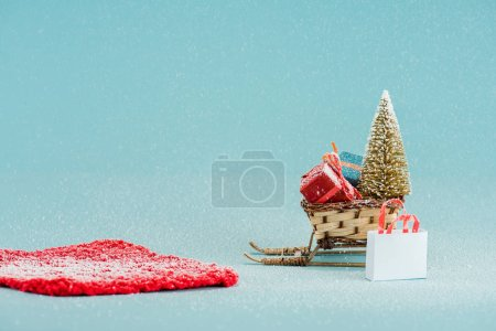 Photo for Red carpet and wicker sled with christmas tree and gift boxes on blue background - Royalty Free Image