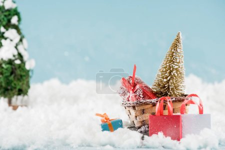 Photo pour Gift boxes and christmas tree in wicker sled, shopping bags in snow - image libre de droit