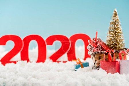 Photo pour Foyer sélectif de traîneau en osier avec arbre de Noël, boîtes-cadeaux, sacs à provisions et numéros 2020 sur fond - image libre de droit