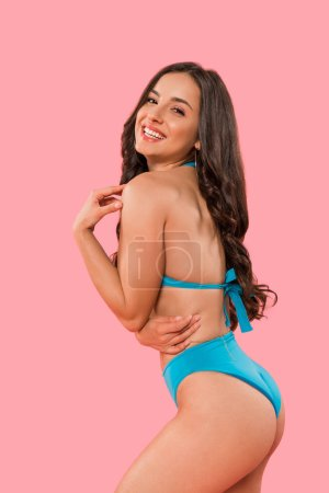 Photo pour Happy woman in swimsuit smiling isolated on pink - image libre de droit