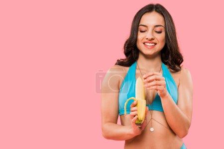 Photo pour Joyeuse jeune femme pelant banane isolée sur rose - image libre de droit