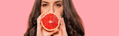 Photo for Panoramic shot of woman in swimsuit covering face with half of grapefruit isolated on pink - Royalty Free Image