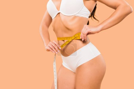 Photo for Cropped view of woman in underwear measuring waist isolated on beige - Royalty Free Image