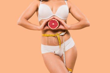 Photo pour Crochet vue d'une femme en sous-vêtements tenant du pamplemousse isolé sur beige - image libre de droit