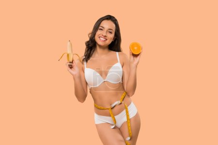 Photo for Cheerful woman holding banana and orange isolated on beige - Royalty Free Image