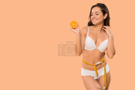 Photo for Cheerful woman in white underwear looking at orange isolated on beige - Royalty Free Image