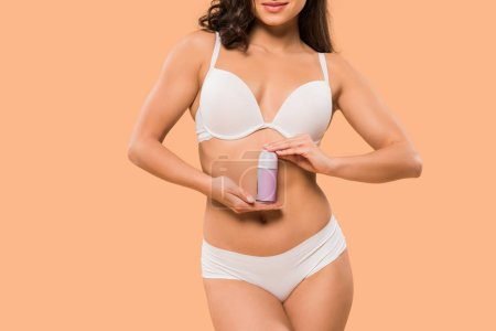 Photo pour Crochet d'une femme tenant un rouleau de déodorant isolé sur beige - image libre de droit