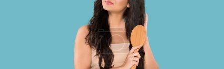 Photo pour Plan panoramique de fille brossant les cheveux brillants isolés sur bleu - image libre de droit