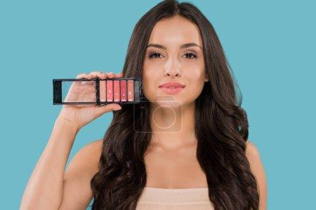 Photo pour Belle femme tenant la palette brillante des lèvres isolée sur bleu - image libre de droit
