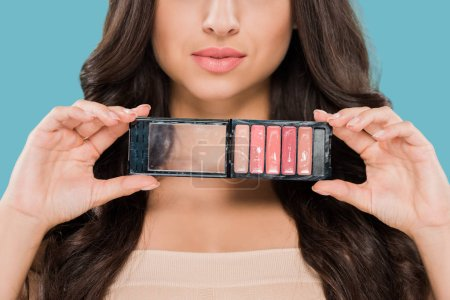Photo for Cropped view of woman holding lip gloss palette isolated on blue - Royalty Free Image