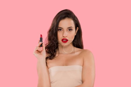 Photo pour Attractive woman with red lips holding lipstick isolated on pink - image libre de droit