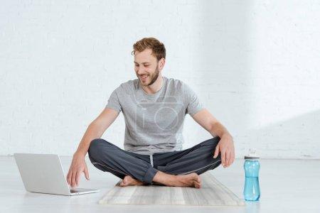 Photo pour Homme souriant assis dans la pose facile près de l'ordinateur portable et bouteille de sport - image libre de droit