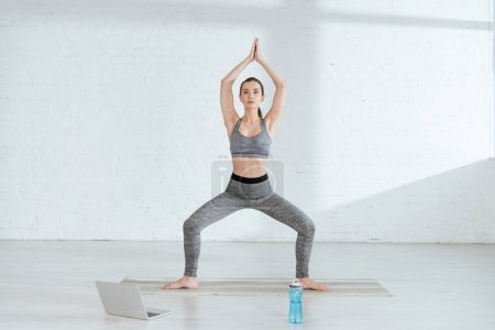Photo for Young woman in sportswear practicing yoga in goddess pose with raised prayer hands - Royalty Free Image
