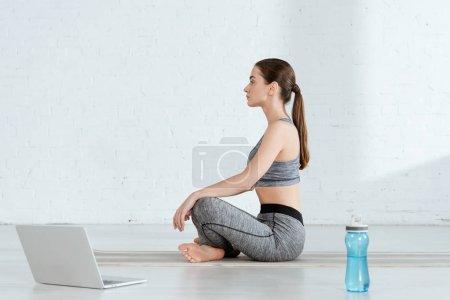 Photo pour Vue latérale d'une jeune femme en tenue de sport pratiquant le yoga en pose facile - image libre de droit