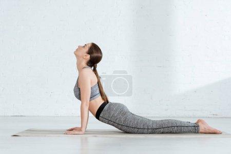 Photo pour Vue latérale d'une jeune femme en tenue de sport pratiquant le yoga en pose de cobra haut - image libre de droit