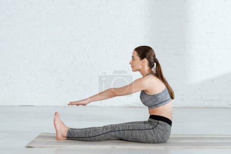 Photo pour Vue latérale d'une jeune femme en tenue de sport s'entraînant au yoga en position coudée vers l'avant - image libre de droit