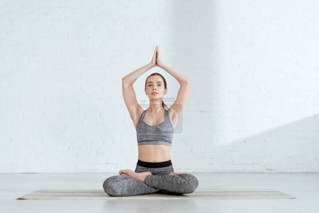 Photo pour Jeune femme en tenue de sport pratiquant le yoga en pose de lotus avec des mains de prière soulevées - image libre de droit