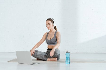 Photo for Young woman in headphones sitting in easy pose near laptop and sports bottle - Royalty Free Image