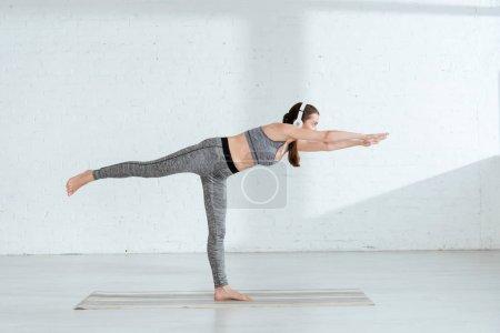 Photo pour Jeune femme dans des écouteurs pratiquant le yoga en guerrier Iii pose - image libre de droit