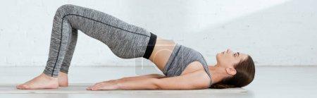 Photo pour Une jeune femme en tenue de sport s'exerce au yoga en pose de planche vers le haut - image libre de droit