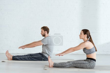 Photo for Side view of man and woman practicing yoga in seated forward bend pose - Royalty Free Image