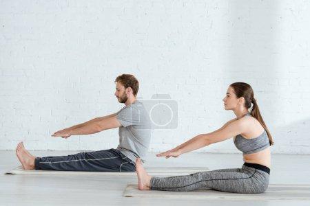 Photo pour Vue latérale de l'homme et de la femme pratiquant le yoga en position coudée vers l'avant - image libre de droit