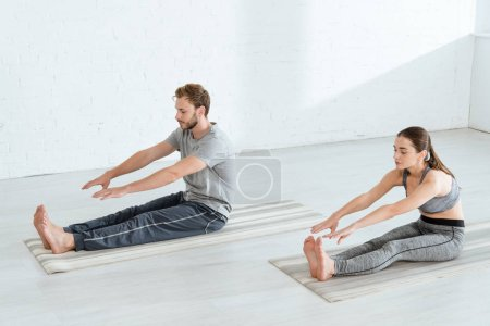 Photo for Young man and woman practicing yoga in seated forward bend pose - Royalty Free Image