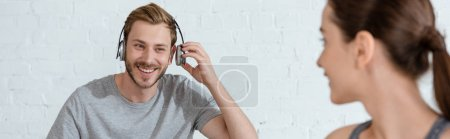 Foto de Enfoque selectivo de la mujer joven mirando al hombre alegre en los auriculares, tiro panorámico. - Imagen libre de derechos
