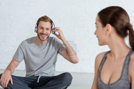 Foto de Enfoque selectivo de la mujer joven mirando al hombre alegre en los auriculares sentados en una posición fácil. - Imagen libre de derechos