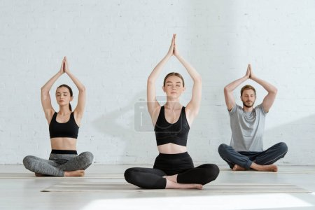 Photo for Young men and woman practicing yoga in half lotus pose with raised prayer hands - Royalty Free Image