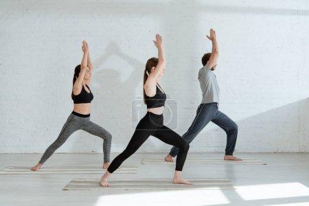 Photo pour Jeunes hommes et jeunes femmes pratiquant le yoga en guerrier je pose - image libre de droit