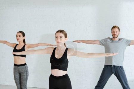 Photo pour De jeunes hommes et femmes pratiquant le yoga en pose à bras ouverts en montagne - image libre de droit